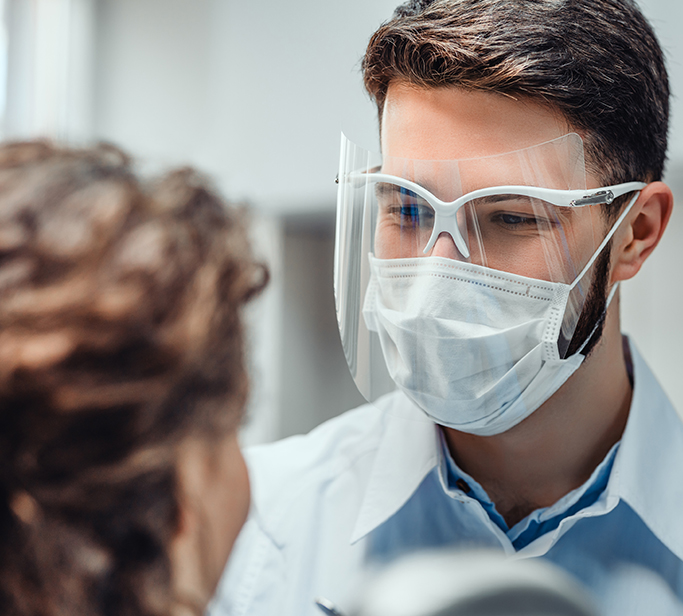 Smiling male healthcare worker wearing safety glasses, face shield and mask while treating patient